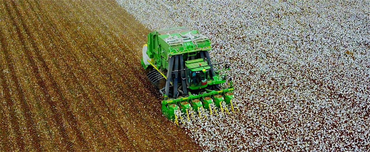 Cotton Baler working in a cotton field.